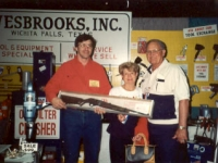Mike Grauerholz of Wesbrooks, Inc. presenting the rifle to the lucky winners at the 1993 NATSO Truck Stop Show in Orlando.